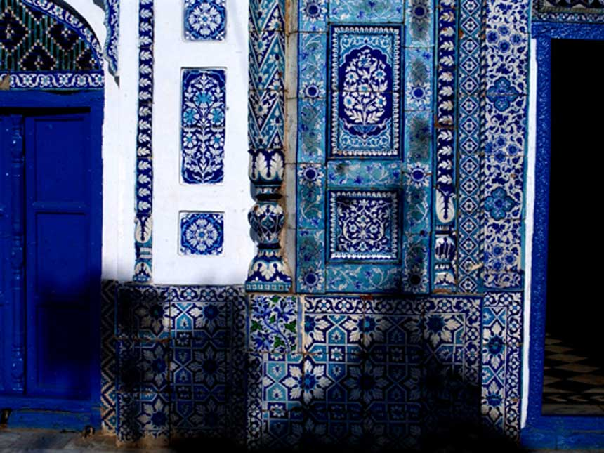 THE BLUES OF BHIT SHAH <br /> Shah Abdul Latif Bhittai's Shrine, Bhit Shah, Sindh<br />  Elaborate kashi tiles in shades of blue decorate the surfaces of Shah Abdul Latif Bhittai's shrine, which is built in typical Sindhi style with limestone domes, minarets, tile and mirror work. Shah Abdul Latif Bhittai is a revered Sindhi saint and poet; he renounced material comforts, and chose a bhit or sand dune on which to sit and meditate. His poems have been compiled in a collection entitled Shah Jo Risalo.<br />  Photogra