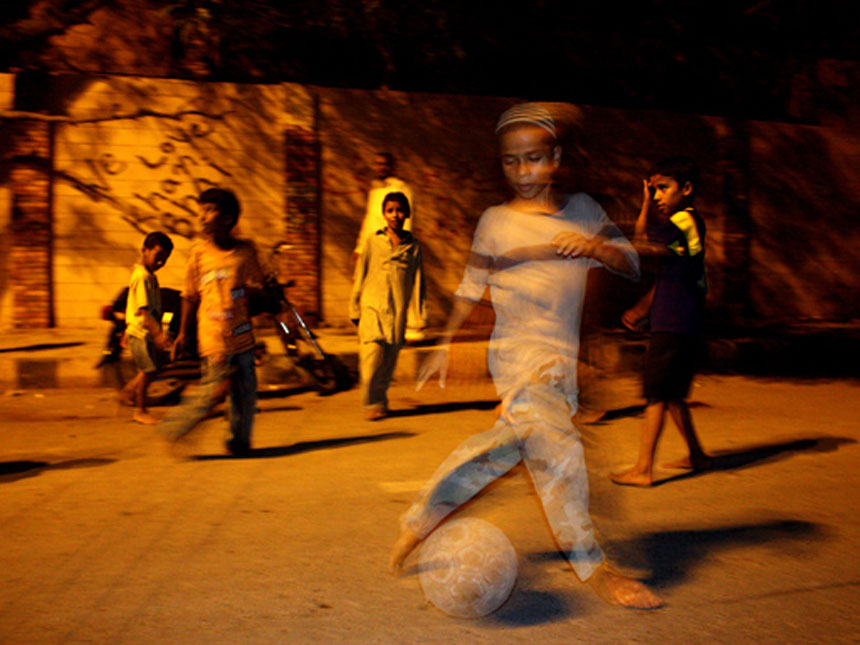 A LEAGUE OF HIS OWN<br /> Lyari, Karachi, Sindh<br />  A young boy from Karachi's poverty and trouble stricken locality of Lyari dribbles a football, barefoot in the street. Football is a favourite sport in the neighbourhood but most young boys are forced to play in the street due to a lack of dedicated recreational spaces.<br />  Photographer:  Hussain Afzal