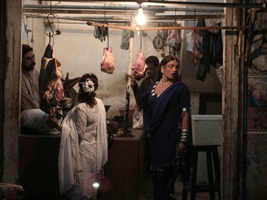 MEAT MARKET<br /> Karachi, Sindh<br />  Two transgender persons (hijras) loiter outside a butcher's stall in Karachi. A marginalised group, they often live in communities headed by a guru; while historically hijras were the special group of people who were given access to the harems in royal courts, today they are reduced to prostitution, begging and performing at ceremonies for a living.<br />  Photographer: Kohi Marri
