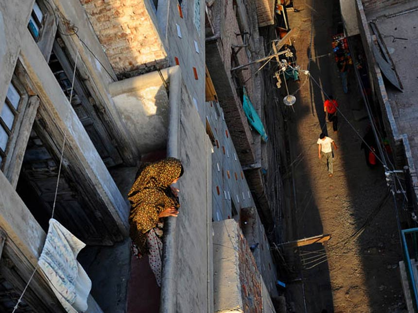 TERRACE VIEW<br /> Walled City, Lahore, Punjab<br />  In Lahore's Walled City, a woman standing in her balcony peers into the narrow street below. Originally the City could be accessed through 13 gates, although some have been destroyed. Several multistoried red brick havelis with carved wooden balconies and overhanging windows are also located in the Walled City.<br />  Photographer: Mahmood Qureshi