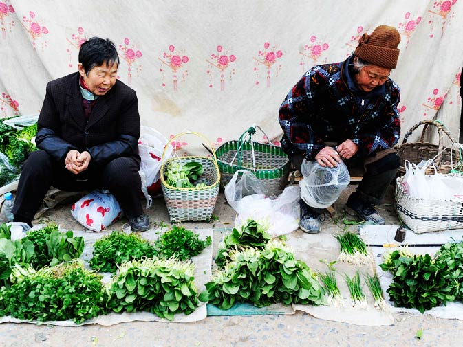 Vendors wait for customers at an open-air market in Hefei, Anhui province, December 11, 2010.