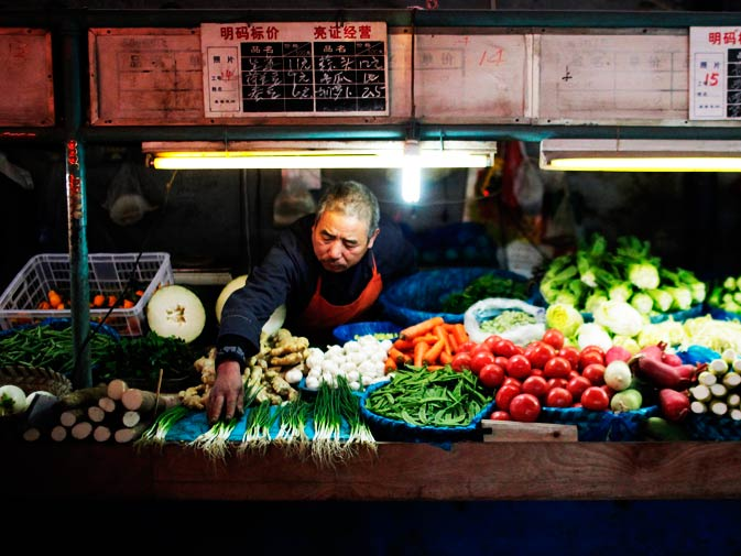 A vendor displays vegetables at a local food market.