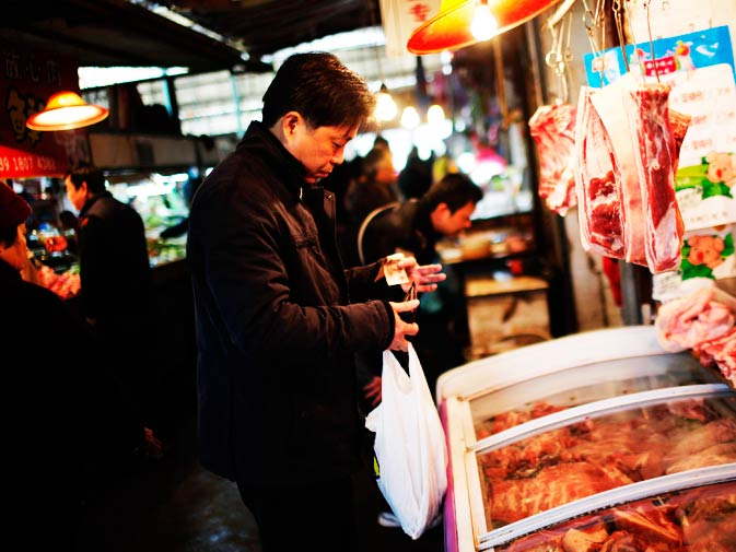 A man buys meat at a local market.