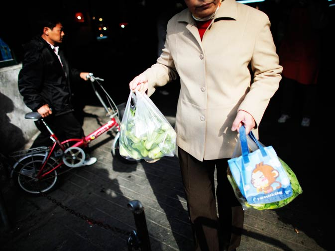 A woman carries bags of vegetables as she leaves a local food market.