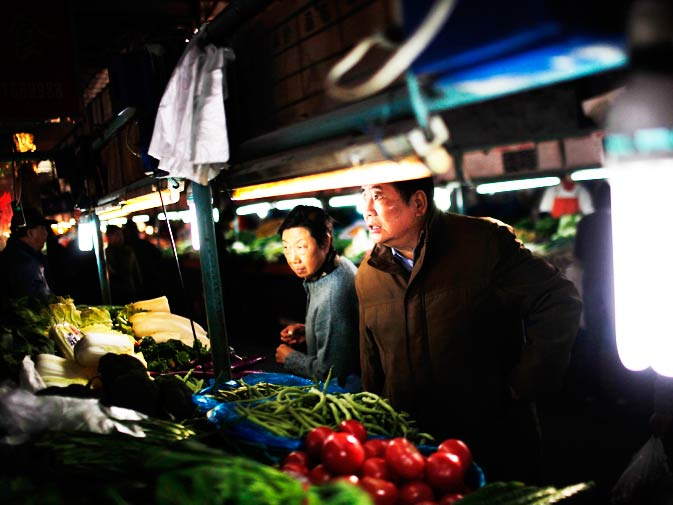 People look for prices of vegetables at a market in Shanghai.
