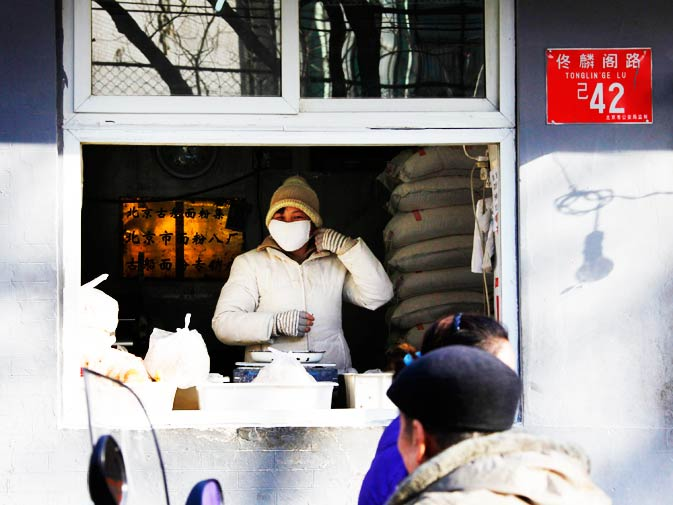 A woman selling noodles adjusts her face mask as customers walk past her shop in central Beijing, December 13, 2010.