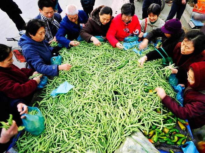 People select French beans from a truck at an open-air market in Xiangyang, Hebei province.