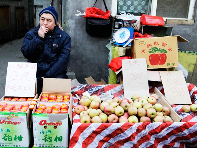 A fruit-seller smokes as he waits for customers at an open-air market in a Hutong area in Beijing.