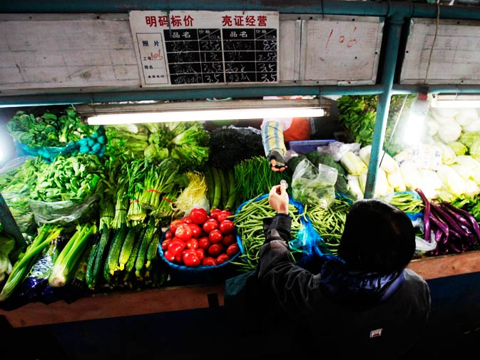 A woman buys vegetables at a local food market in Shanghai.