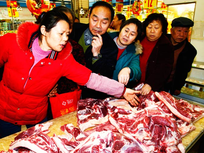 Customers select pork at a market in Suining, Sichuan province.