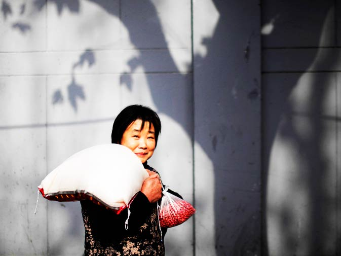 A woman carries a bag of rice and a packet of beans as she leaves a local food market in Shanghai.