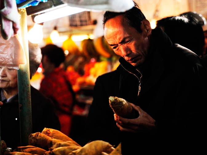 A man buys vegetables at a local market.