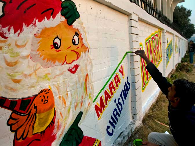 Kaleem Masih paints Santa Claus and a Christmas message on a wall as he and others decorate their colony ahead of Christmas celebrations in Islamabad. ? AP