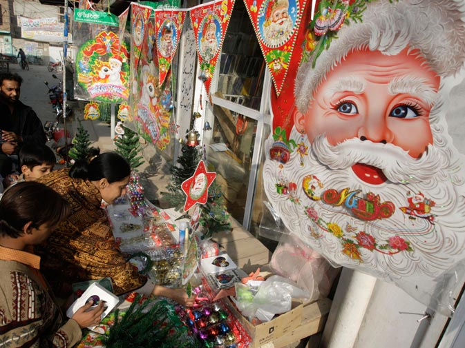 People buy Christmas items from a shop in a Christian neighborhood in Lahore, Pakistan. ? AP