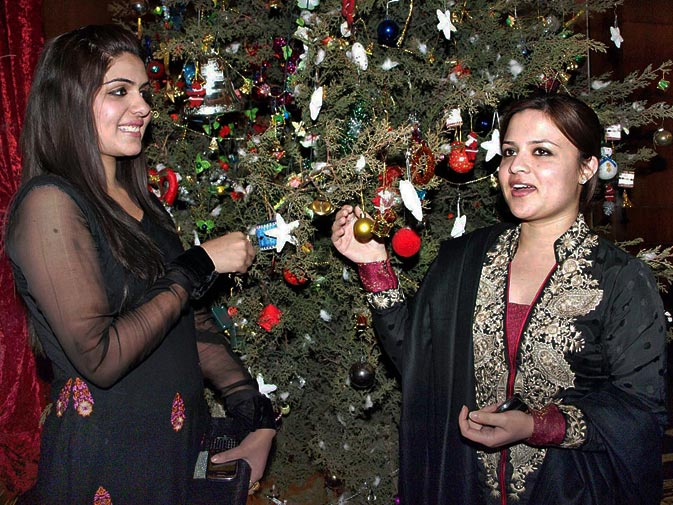 Girls pose next to a Christmas tree in a reception hall of a local hotel in Rawalpindi. ? ONLINE