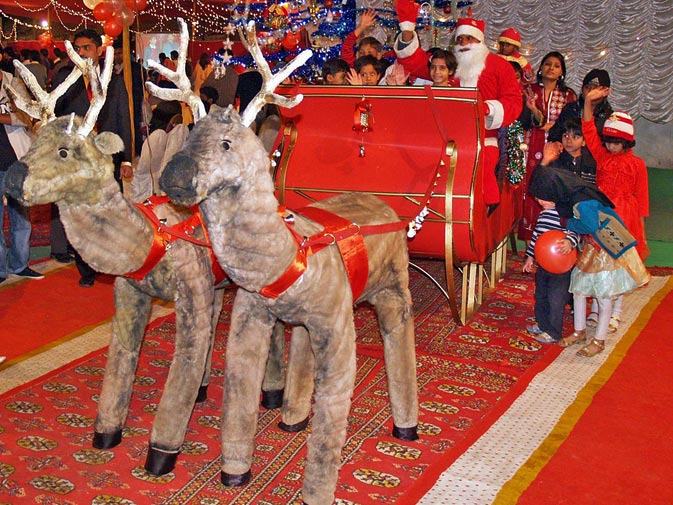 Children sit with Santa Clause on a mock reindeer ride during a ceremony in Karachi. ? ONLINE