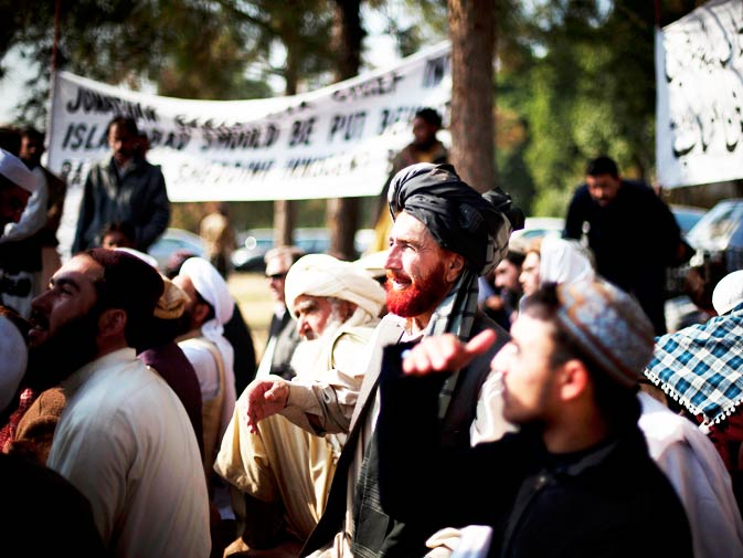 Villagers from the Waziristan tribal region sit in protest near the Parliament in Islamabad, on Thursday, Dec. 9, 2010. Banner on right reads ?Chief Justice should take notice?.