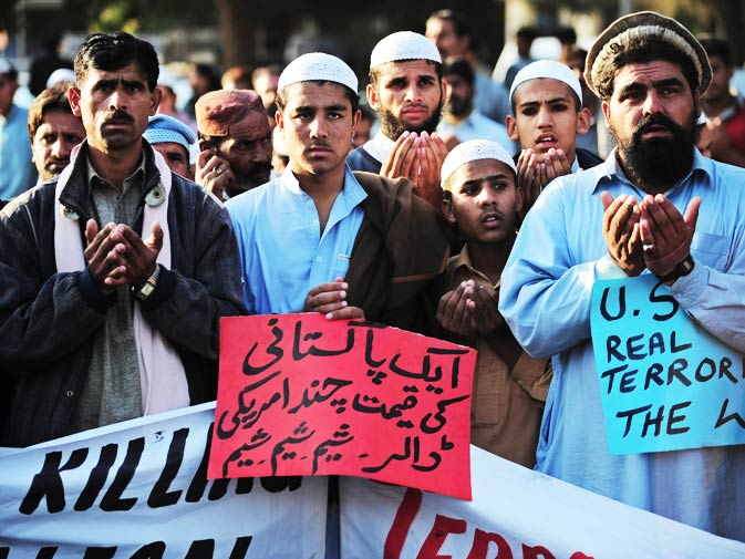 Religious students and tribesmen of North Waziristan pray in Islamabad on December 10, 2010, on the second day of protests against the US drone attacks.