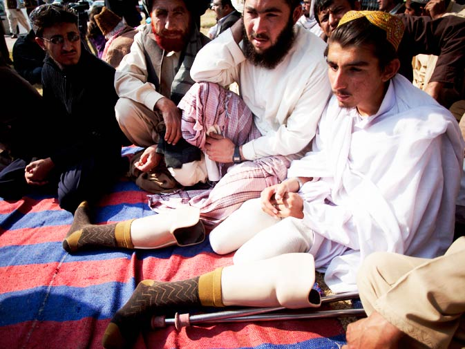 Villagers sit with Sanaullah, right, from the tribal area of Waziristan, who reportedly lost his legs and an eye by a US drone attack, during the protest.