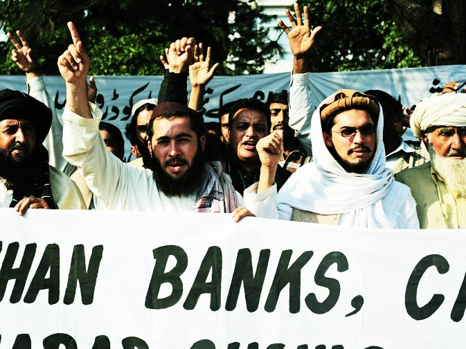 Tribesmen shout slogans as they hold a banner during the protest.