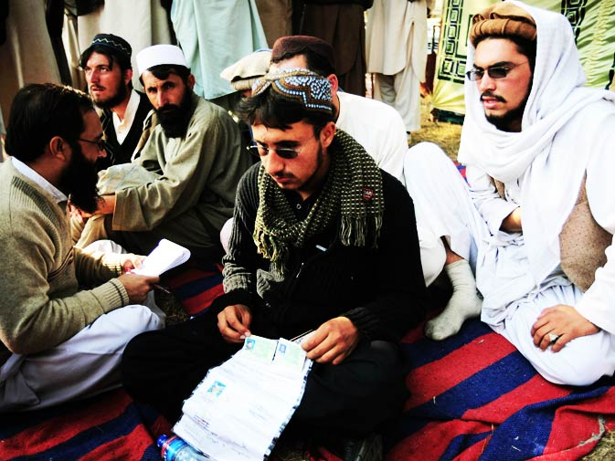 Tribal student Mohammad Fahim (C), who lost his eye in a US drone attack sits along with others during the protest.