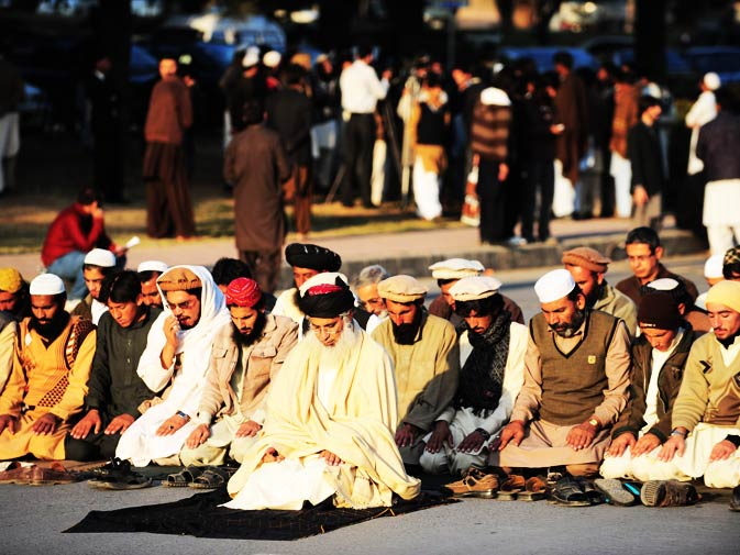 Cleric Abdul Aziz (C) leads a prayer with tribesmen of North Waziristan, on a street in Islamabad on December 10, 2010, on the second day of protests against US drone attacks.