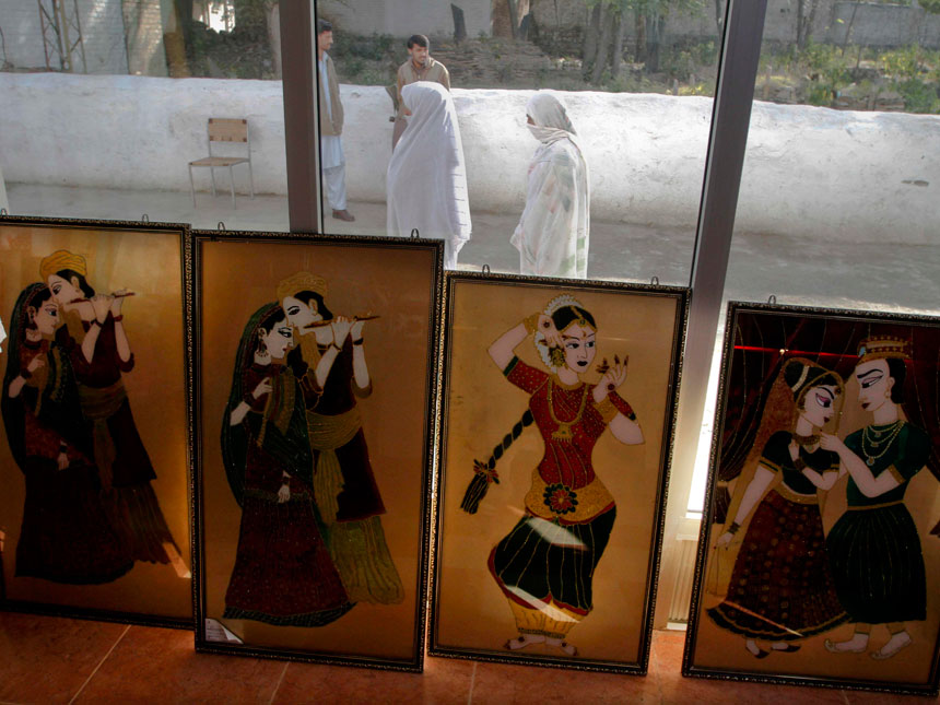 In this image taken on Dec. 2, 2010 girls walk past paintings prepared at a vocational school in  Mingora, Pakistan. Most of the 2   million who fled Taliban oppression and the fighting to oust them have returned. ? AP