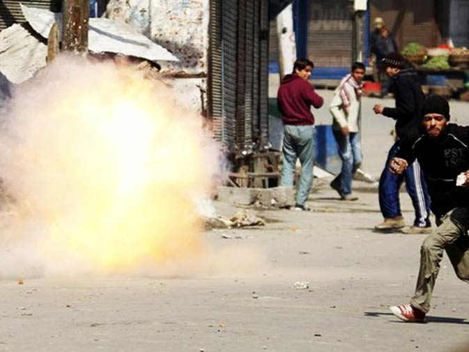 A Kashmiri protester runs as a tear gas shell fired by the Indian police explodes during an anti-Indian protest in Srinagar February 20, 2010. Indian police in Srinagar used tear smoke shells to disperse Kashmiri protesters during a strike called by the region's hardliner faction of the Hurriyat (Freedom) Conference against what Hurriyat says is the continuous human rights violation on Kashmiri people by Indian security forces. - Photo by Reuters.