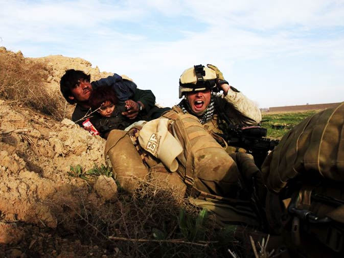 US Marine Lance Corporal Chris Sanderson, 24, from Flemington, New Jersey shouts as he tries to protect an Afghan man and his child after Taliban fighters opened fire in the town of Marjah, in Nad Ali district, Helmand province February 13, 2010. - Photo by Reuters.