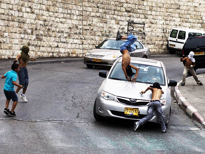An Israeli motorist runs down a masked Palestinian youth who was standing among a group of youngsters throwing stones at Israeli cars on October 8, 2010 in the mostly Arab east Jerusalem neighborhood of Silwan. - Photo by AFP.