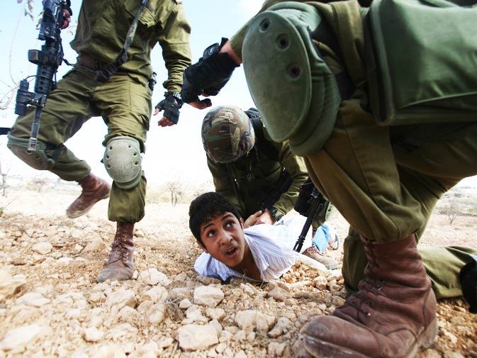 A Palestinian youth is arrested by Israeli soldiers for throwing stones during a protest by foreign, Israeli and Palestinian demonstrators against the Jewish settlement of Karmi Tsour close to the Palestinian village of Beit Omar, north of the West Bank town of Hebron, on October 23, 2010. - Photo by AFP.