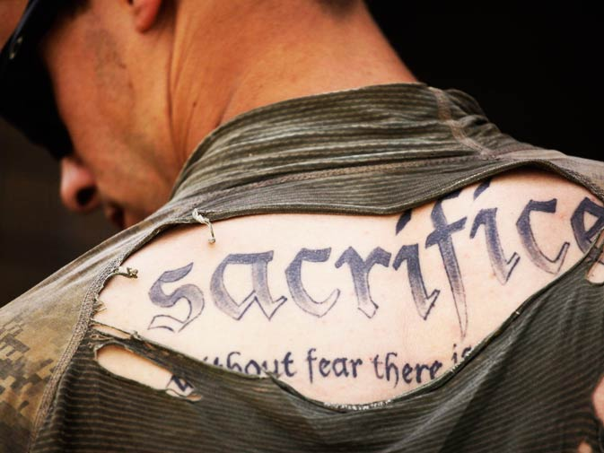 In this May 8, 2010 file photo, a tattoo on the back of US Army Sgt. James Wilkes of Rochester, NY, is seen through his torn shirt after a foot patrol with 1st Platoon, Charlie Company, 2nd Battalion, 1st Infantry Regiment, of the 5th Styker Brigade in Afghanistan's Kandahar province. The full tattoo reads, ?Sacrifice. Without fear there is no courage.? - Photo by AP.