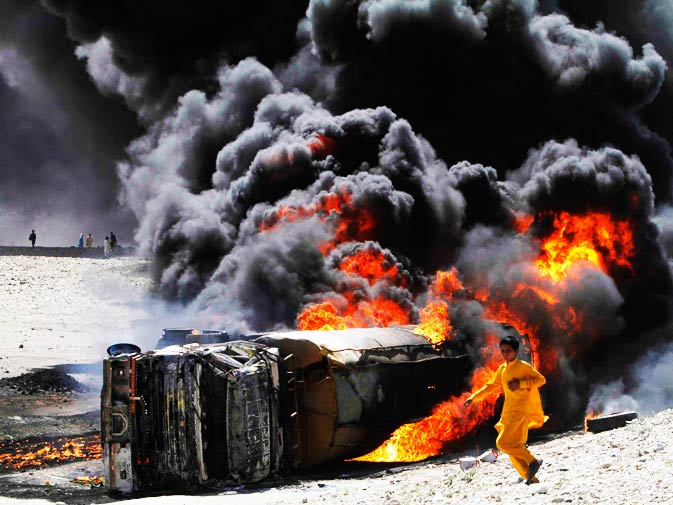 In this May 28, 2010 file photo, an Afghan boy scurries past a burning oil tanker carrying fuel supplies for Nato forces after it was allegedly attacked by Taliban on Jalalabad highway, east of Kabul, Afghanistan. - Photo by AP.