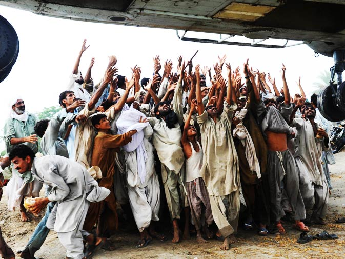 Pakistani flood survivors try to catch food bags from an army helicopter in Lal Pir on August 7, 2010. - Photo by AFP.