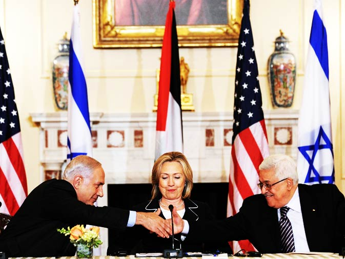 US Secretary of State Hillary Clinton (C), looks on as Prime Minister Benjamin Netanyahu of Israel (L) and President Mahmoud Abbas of the Palestinian Authority (R) shake hands as they re-launch direct negotiations between Israeli and Palestinian Authority at the State Department in Washington, DC, on September 2, 2010. - Photo by AFP.