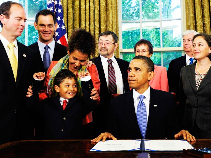 In this May 17, 2010 file photo, Mariane Van Neyenhoff, widow of Wall Street Journal reporter Daniel Pearl, holds up the arms of their son, Adam Daniel Pearl, after President Barack Obama signed the Daniel Pearl Freedom of the Press Act,  in the Oval Office of the White House in Washington. Also attending the ceremony is Rep. Adam Schiff, D-Calif., left, and Sen. Chris Dodd, D-Conn., second from right. - Photo by AP.