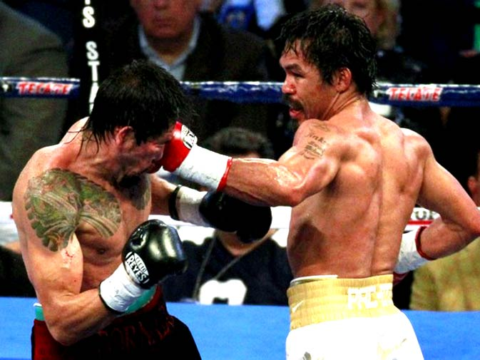 Antonio Margarito of Mexico is hit with a left by Manny Pacquiao (R) of the Philippines in the 5th round of their 12 round WBC World Super Welterweight title boxing fight in Arlington, Texas November 13, 2010. Pacquiao eventually cemented his place in the pantheon of boxing greats by recording an unanimous points victory over Margarito to claim the vacant WBC super welterweight title. - Photo by Reuters.