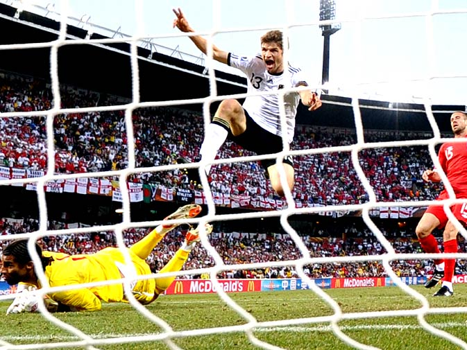 Germany's midfielder Thomas Mueller (C) celebrates as he scores Germany's third goal past England's defender Matthew Upson (R) and England's goalkeeper David James (L) during the 2010 World Cup match Germany vs. England on June 27, 2010 at Free State stadium in Mangaung/Bloemfontein. Germany defeated England 4-1. - Photo by AFP.