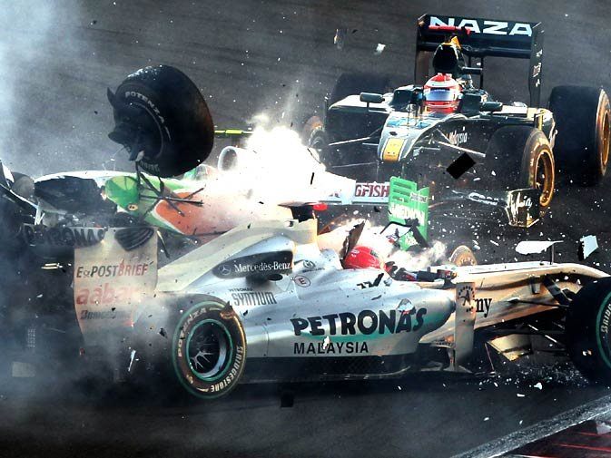 Mercedes GP's German driver Michael Schumacher crashes with Force India's Italian driver Vitantonio Liuzzi  at the Yas Marina circuit on November 14, 2010 in Abu Dhabi, during the Abu Dhabi Formula One Grand Prix. - Photo by AFP.
