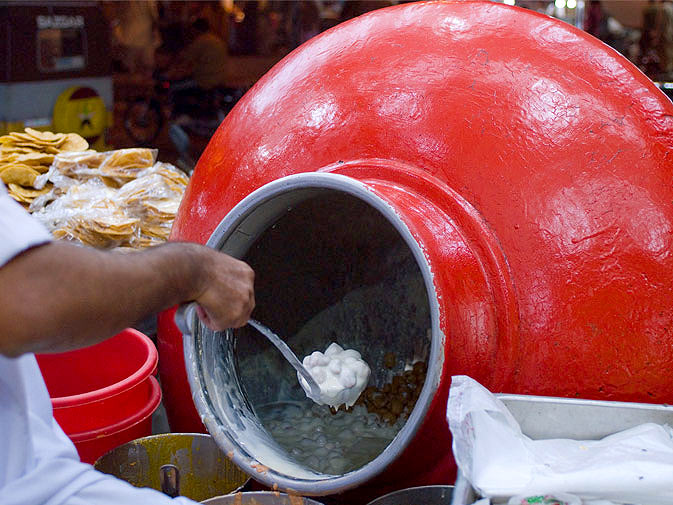 """A vendor takes out a spoonful of """"Dahi Baray"""" from a giant serving-pot. This sweet or salty dessert is made with dumplings in yogurt, and sprinkled with a little masala to spice things up."""