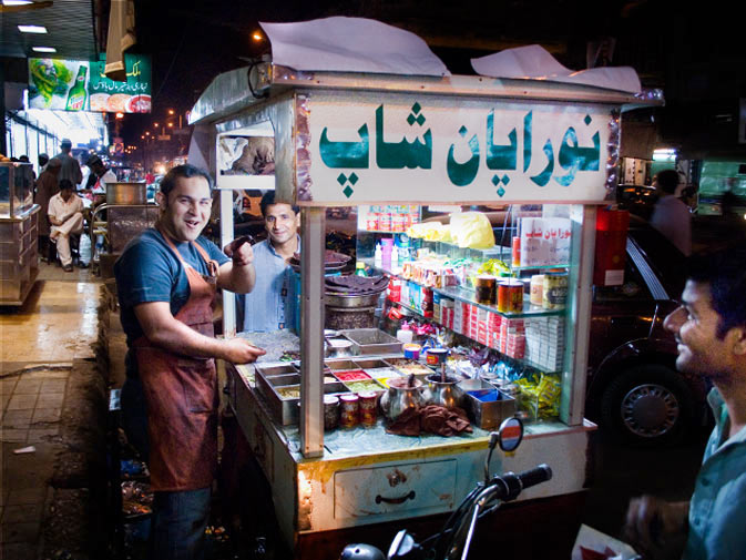 """A heavy meal in Karachi is often followed by a trip to the """"Paan Shop"""". Paan is said to help digestion and freshen breath. Here the owner of 'Noora Paan Shop' jokes with his regulars as he makes them their favorite paans."""
