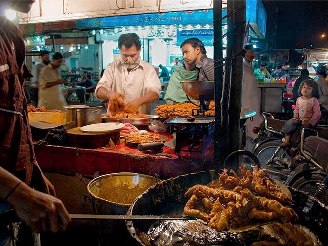 """A fried-fish stand sells raw and cooked fish. The fish is marinated in spicy """"masala"""" and then batter-fried to make a delicious and easy meal."""