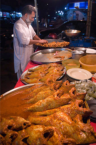 Whole fish lie in the marinade, soaking up the spicy masala before being fried in a large deep-pan.