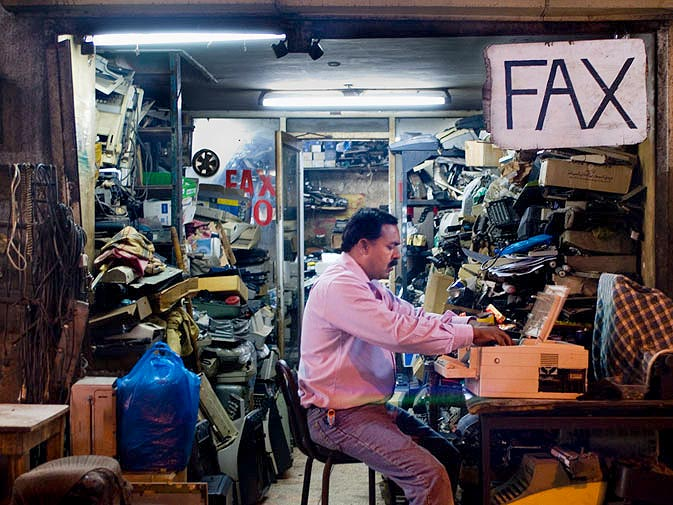 A repairman sits out on the sidewalk and works in front of his shop. Inside there are precariously stacked shelves with piles and piles of old typewriters, printers, telephones and fax-machines.