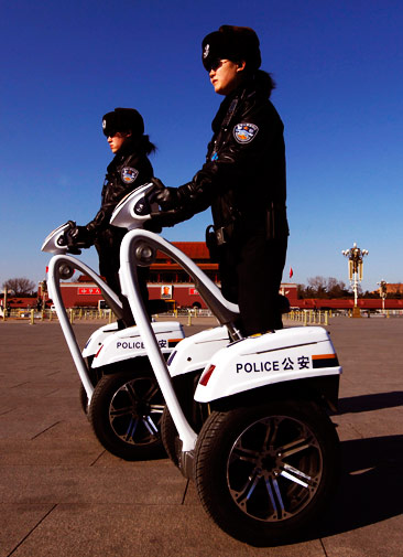 Policewomen ride motorised vehicles at Tiananmen Square.