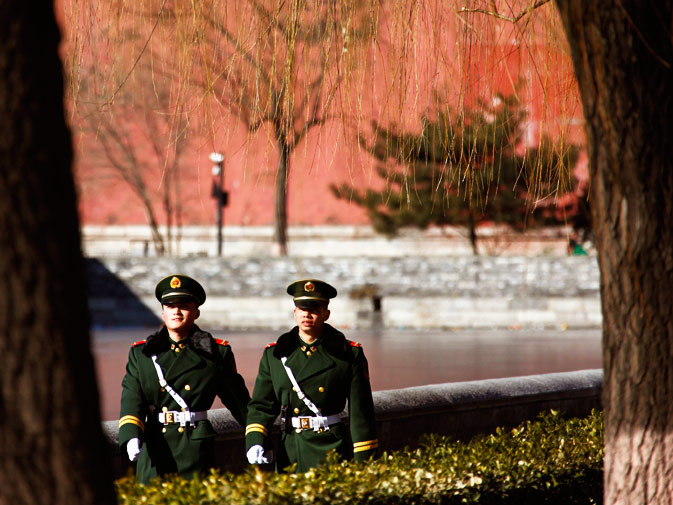 Paramilitary policemen patrol around the Forbidden City.