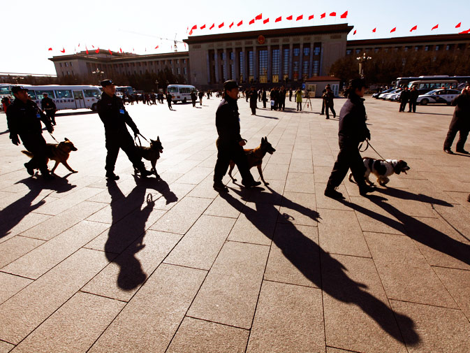 Policemen walk with their dogs at the Tiananmen Square.