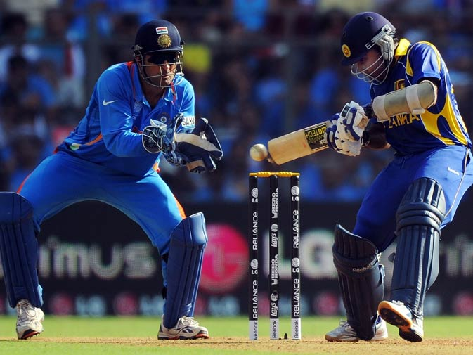 Mahela Jayawardena (R) plays a shot as Mahendra Singh Dhoni (L) watches. ? Photo by AFP
