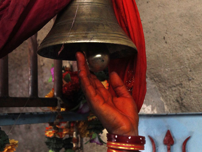A devotee strikes a bell while entering the Shri Hinglaj Mata Temple.