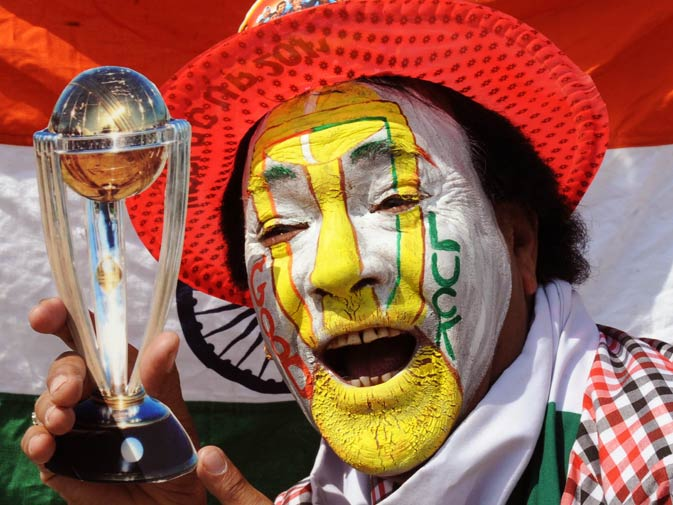 An Indian cricket fan holds a replica Cricket World Cup trophy while cheering for the Indian team ? Photo by AFP